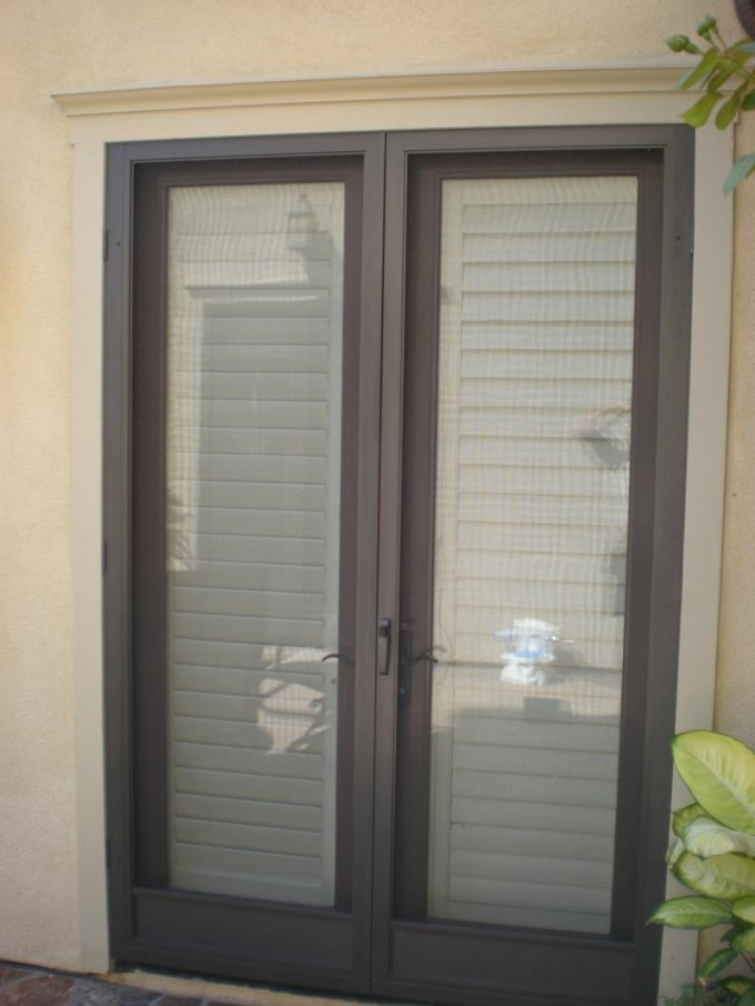 White And Grey Retractable Screen Doors With Cream Wall And Flower