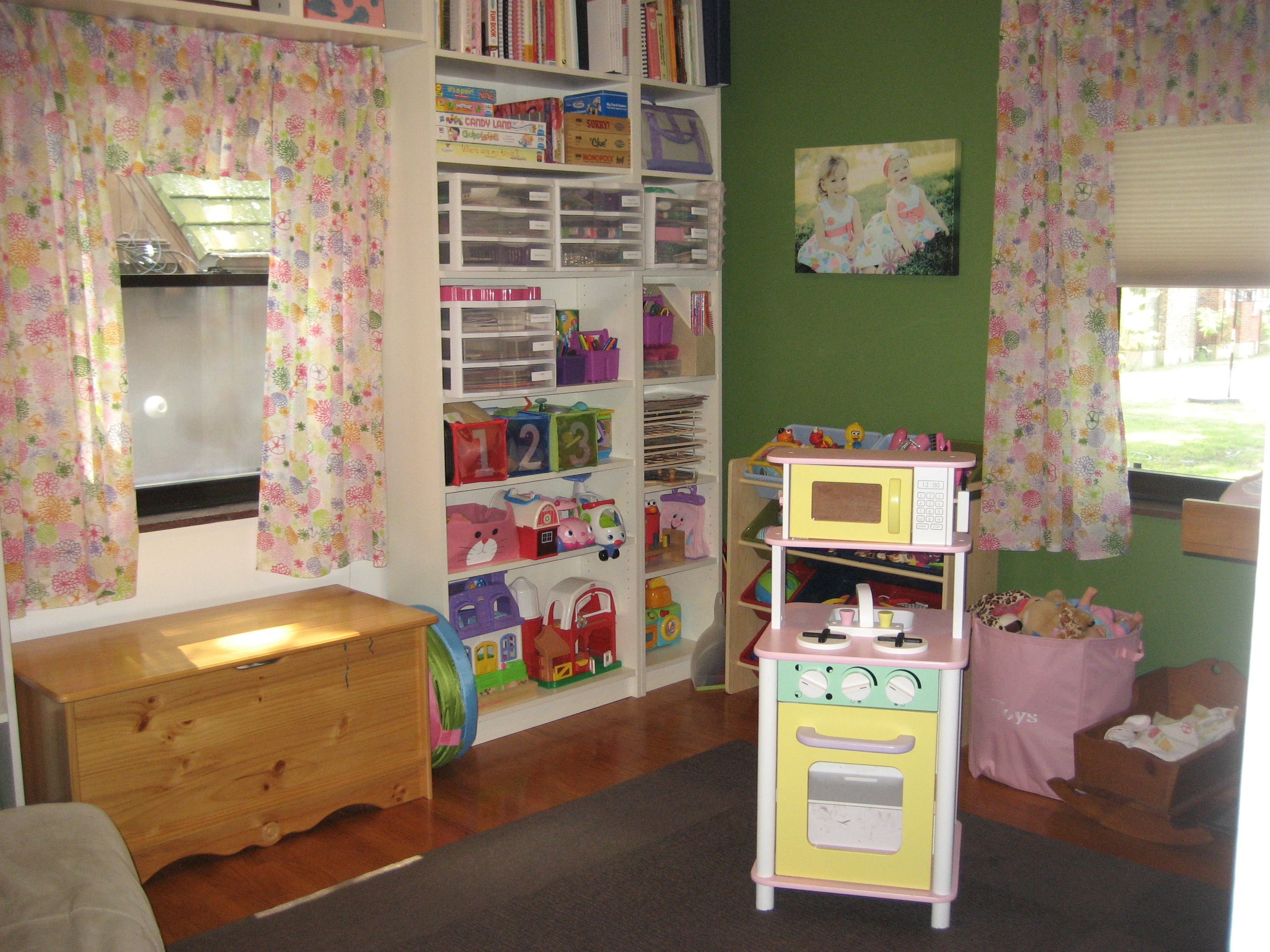 white ikea toy storage filled with children goods matched with green wall plus floral curtains for pretty children room