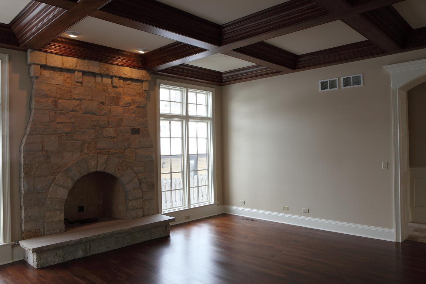 wooden cofferd ceiling matched with white wall and fireplace plus wooden floor for family room design