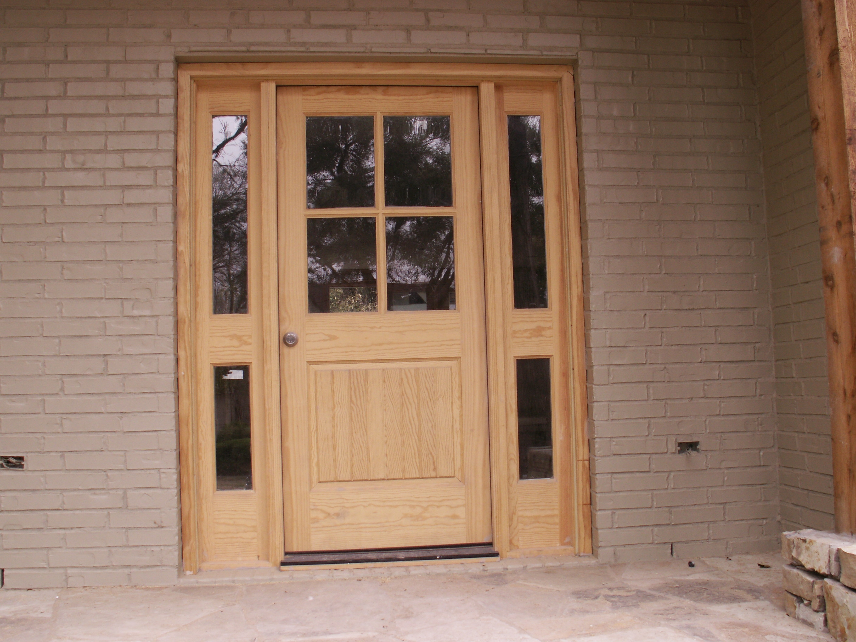 wooden entry door with sidelights with brick wall and ceramic floor