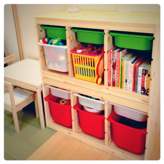 wooden ikea toy storage filled toys and books with desk beside