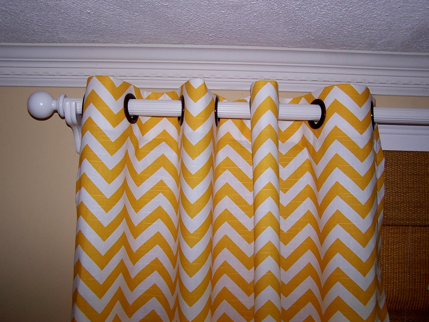 yellow and white chevron curtains with black ring matched with cream wall with white baseboard molding