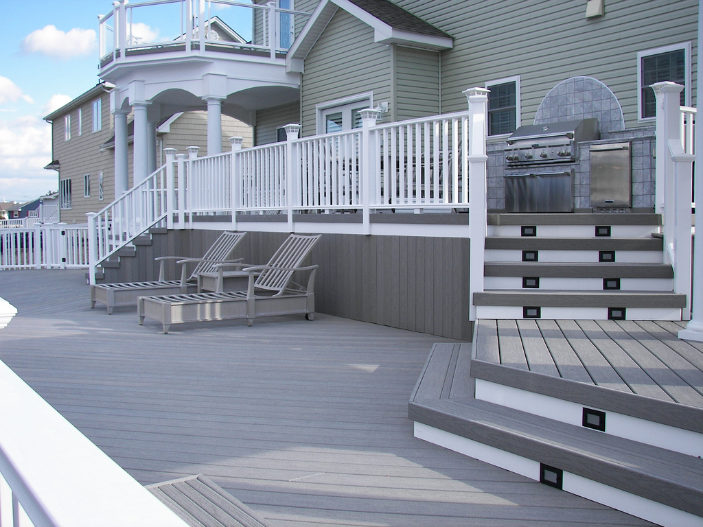a house with grey evergrain decking matched with white railing plus relax chairs ideas
