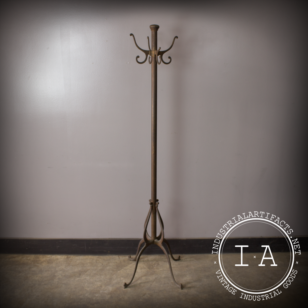 antique standing coat rack on tan floor before gray wall