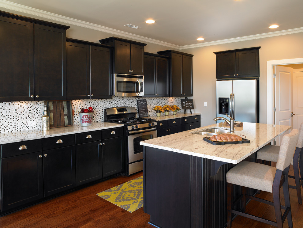 Beautiful black Aristokraft Cabinets With silver handle and mosaic back splash plus oven for kitchen decor ideas