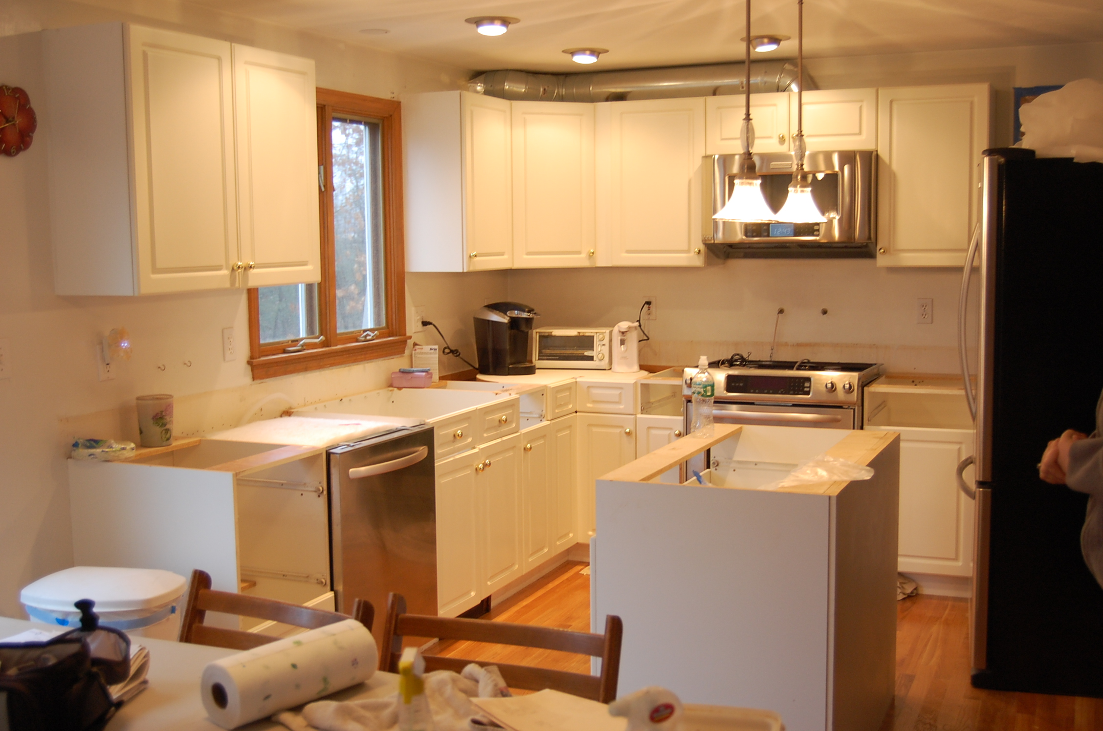 beautiful Kitchen Cabinets Refacing in white with oven and frige plus chandelier and wooden window