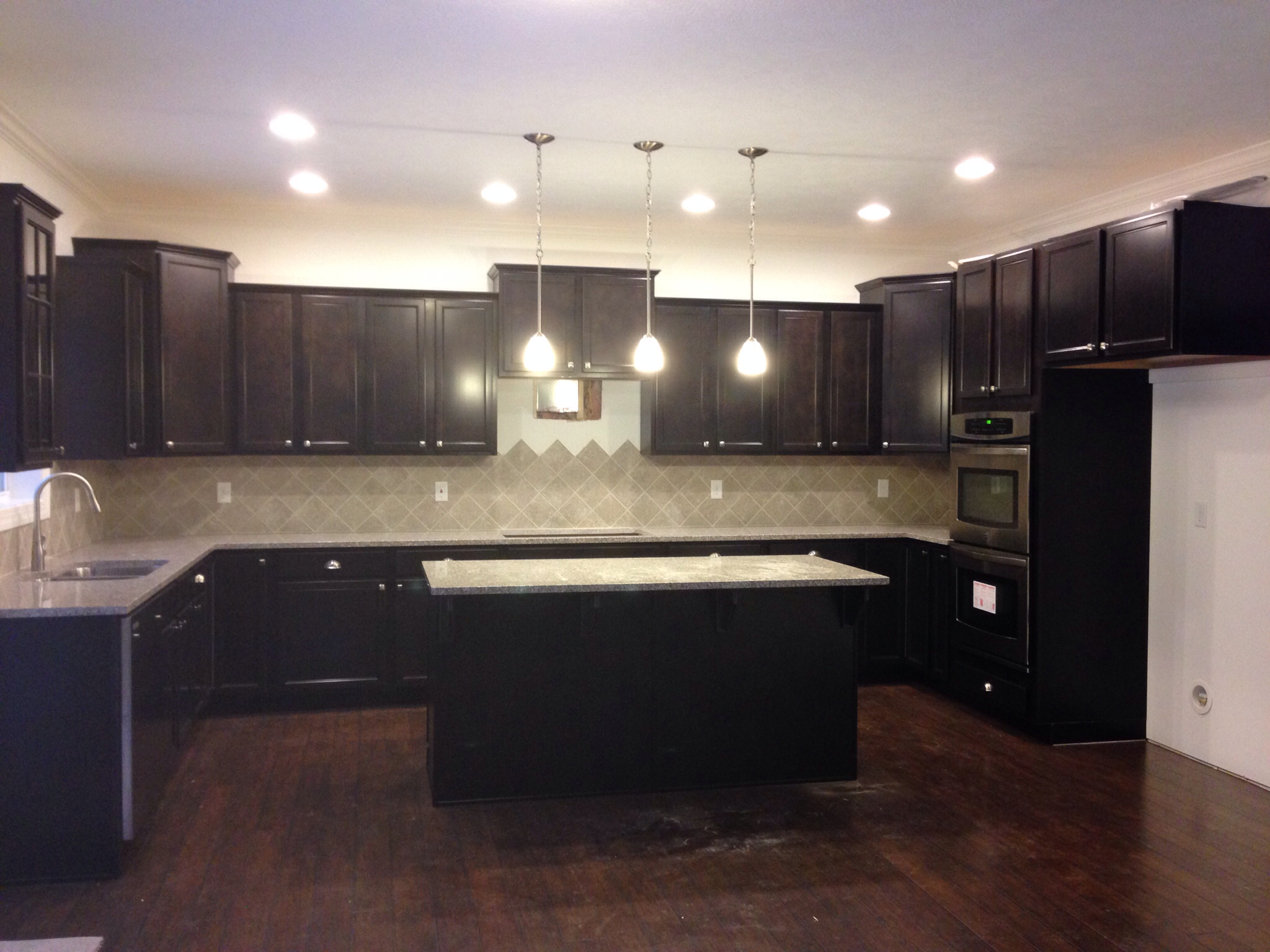 black aristokraft cabinets with beige back splash matched with wooden floor for kitchen design ideas
