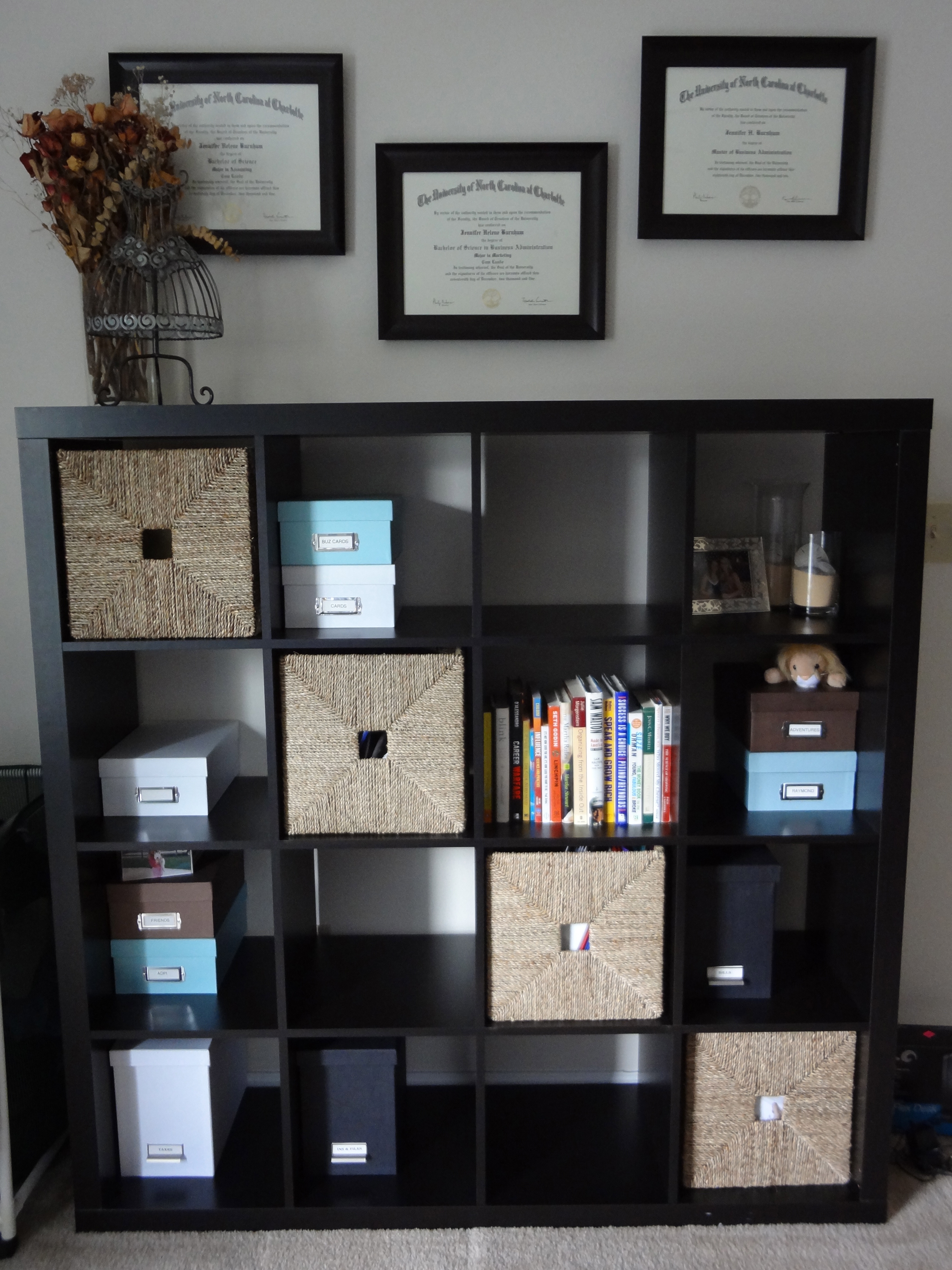 black IKEA Expedit bookcase before white wall plus pictures