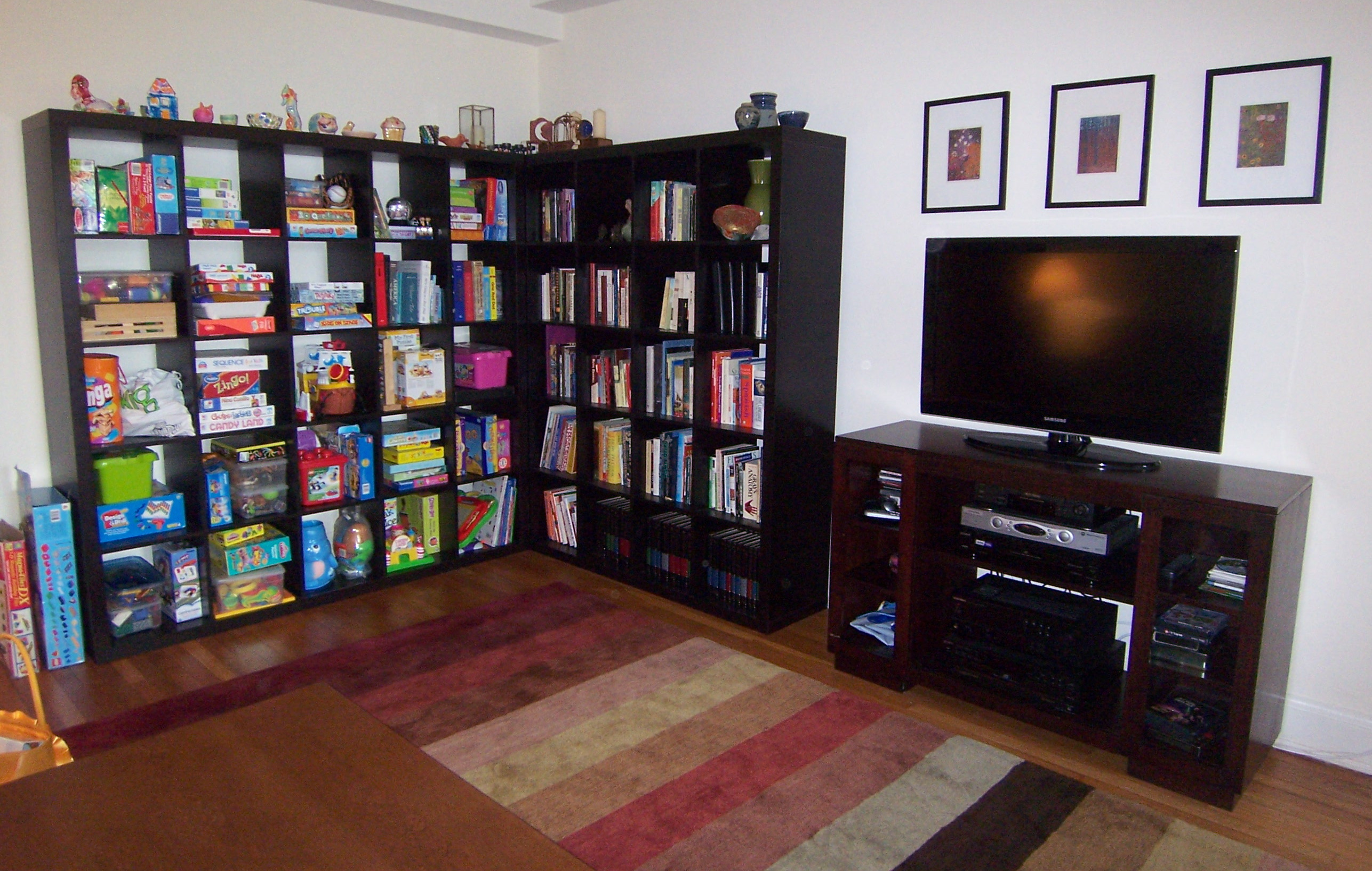 black Ikea expedit bookcase filled with books ideas with pictures on white wall plus computer and multicolor carpet