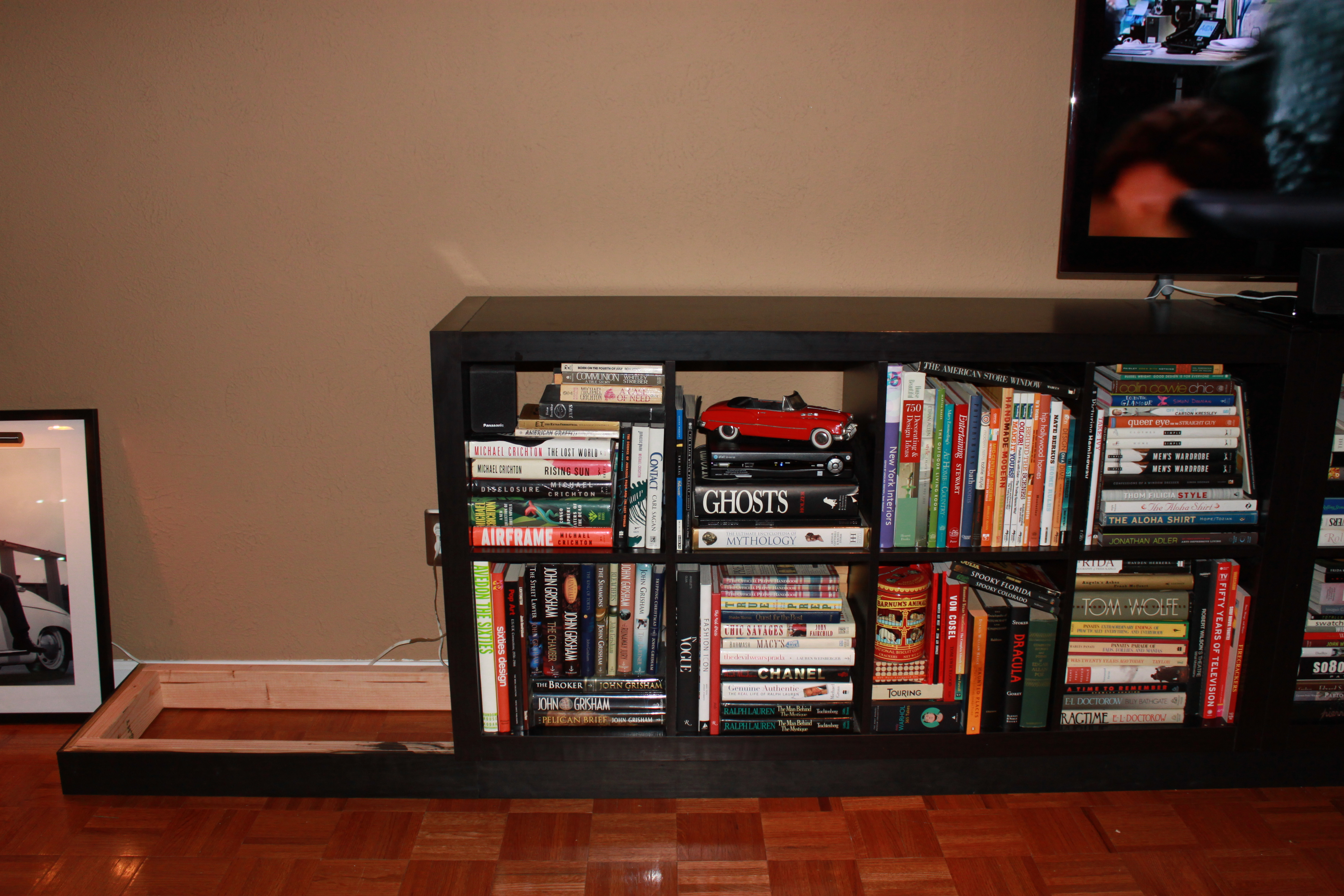 black Ikea Expedit Bookcase filled with books on brown floor with grey wall