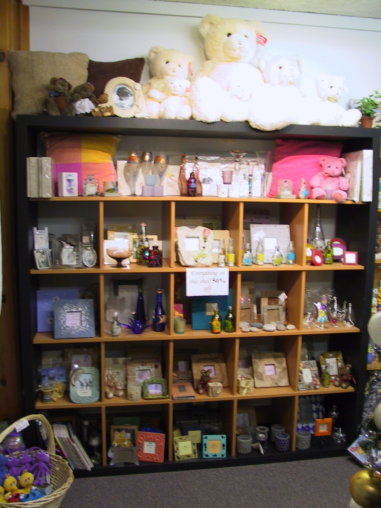 black ikea expedit bookcase filled with frames and doll plus other goods plus teddy bear dolls above