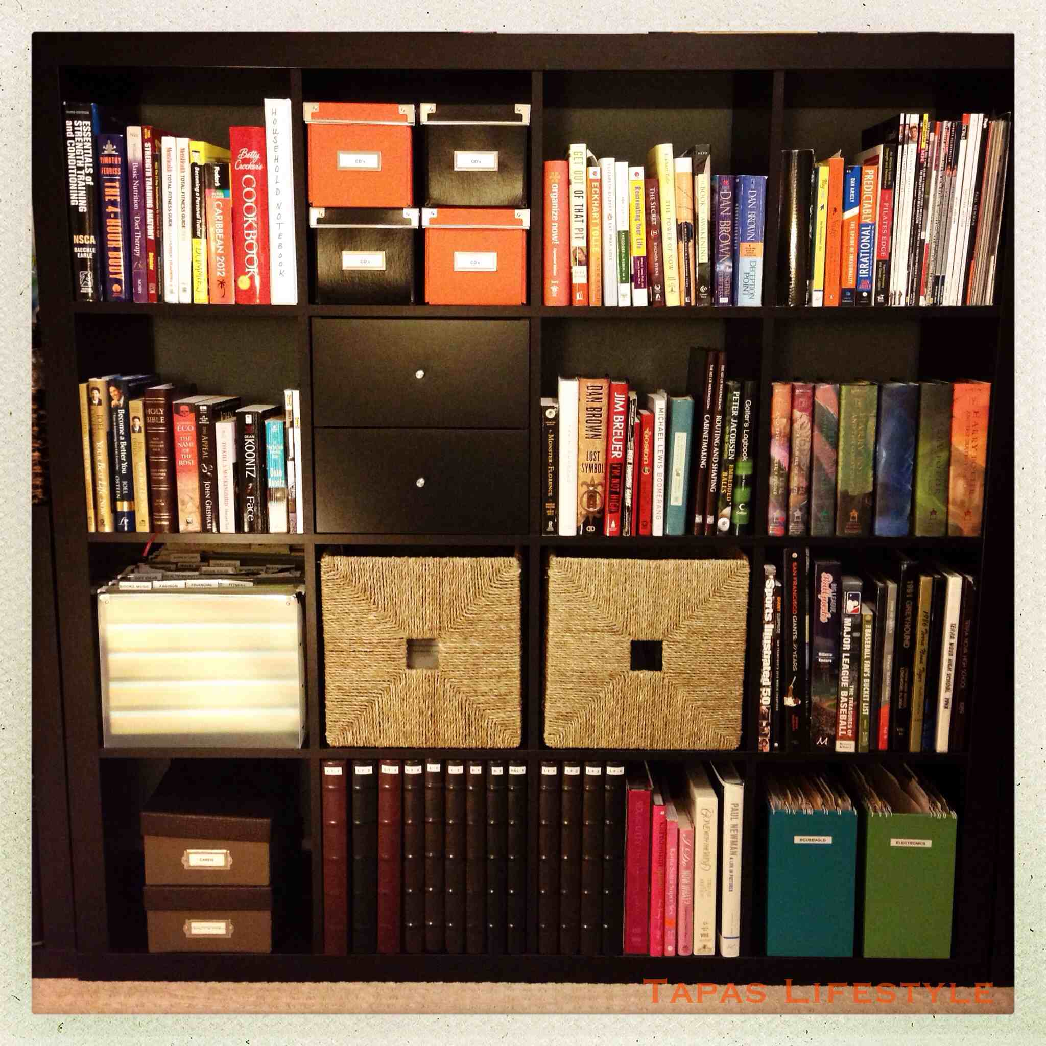 black ikea expedit bookcase filled with many books plus drawers