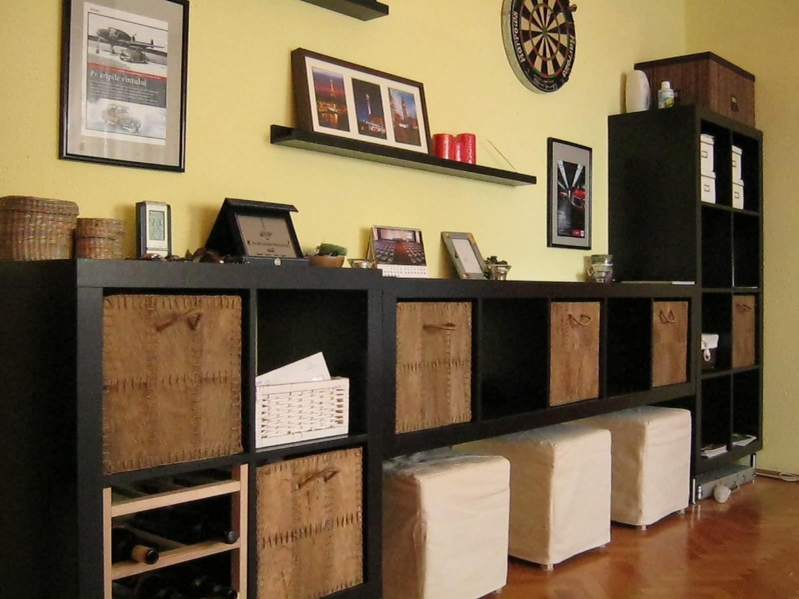 black ikea expedit bookcase with white stool and picture on yellow wall