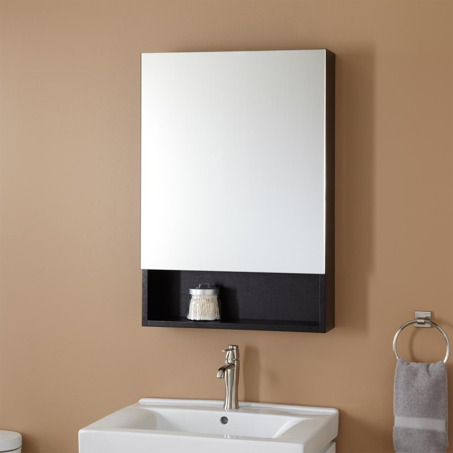 Black Lowes Medicine Cabinets with mirror on tan wall plus white sink and silver faucet