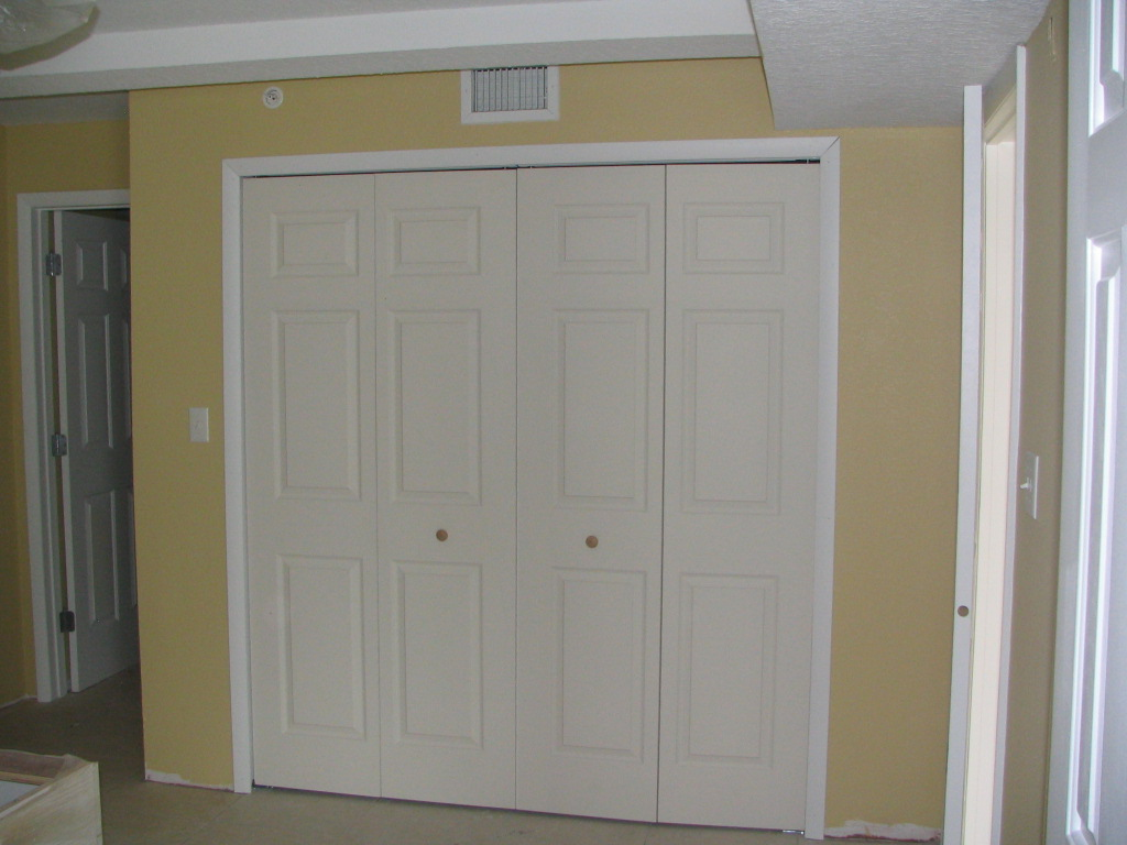 Brilliant Folding Closet Doors On Cream Wall With Ceramics Floor