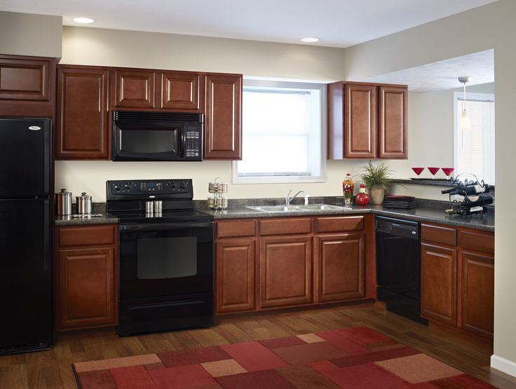 brown aristokraft cabinets matched with white wall plus black oven and wooden floor plus red rectangular carpet for kitchen design ideas