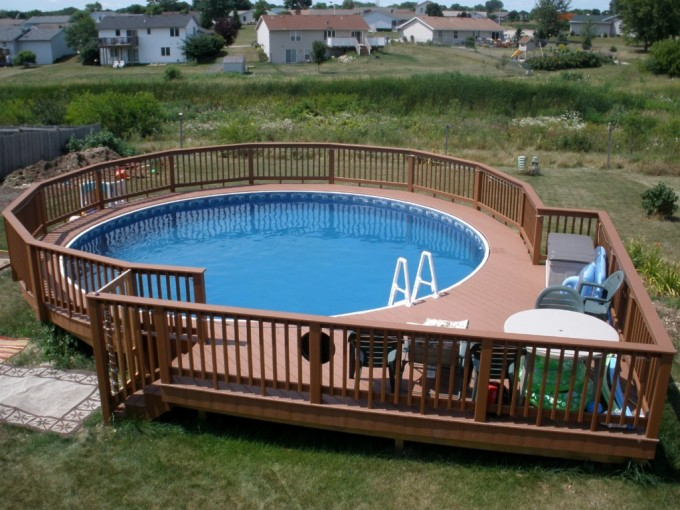 Brown Evergrain Decking Matched With Brown Railing Surround Round Swimming Pool Plus Chairs And Table Ideas