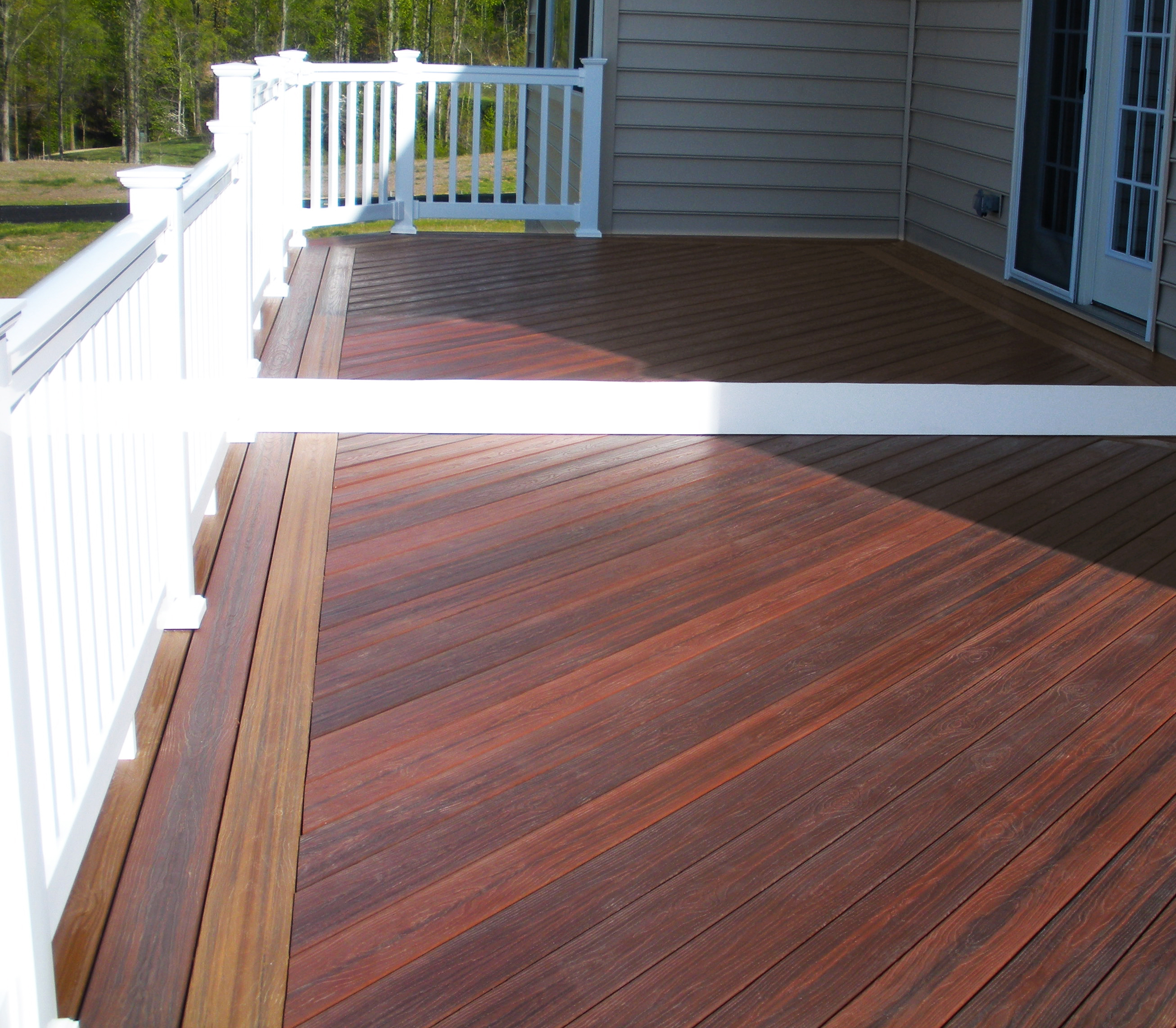 brown evergrain decking matched with white railing and wheat wall for patio decor ideas