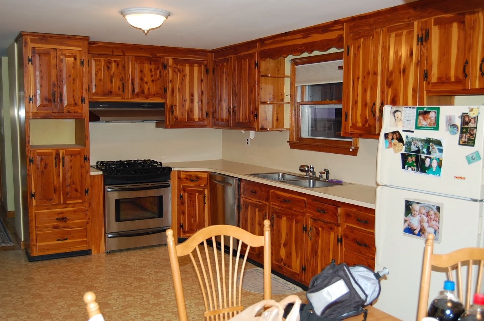 brown Kitchen Cabinet Refacing with sink under wooden single hung window plus white refrigerator and cream floor
