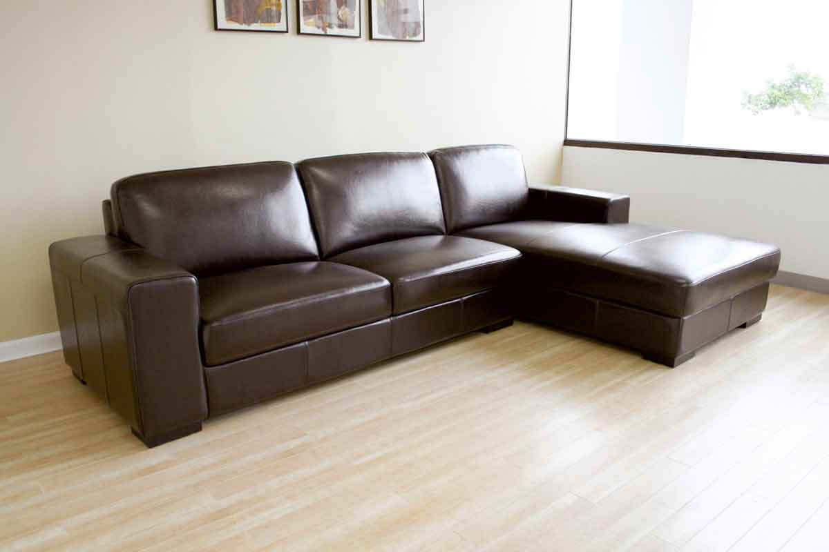 brown leather sectional couches on wooden floor matched with white wall for inspiring living room decor
