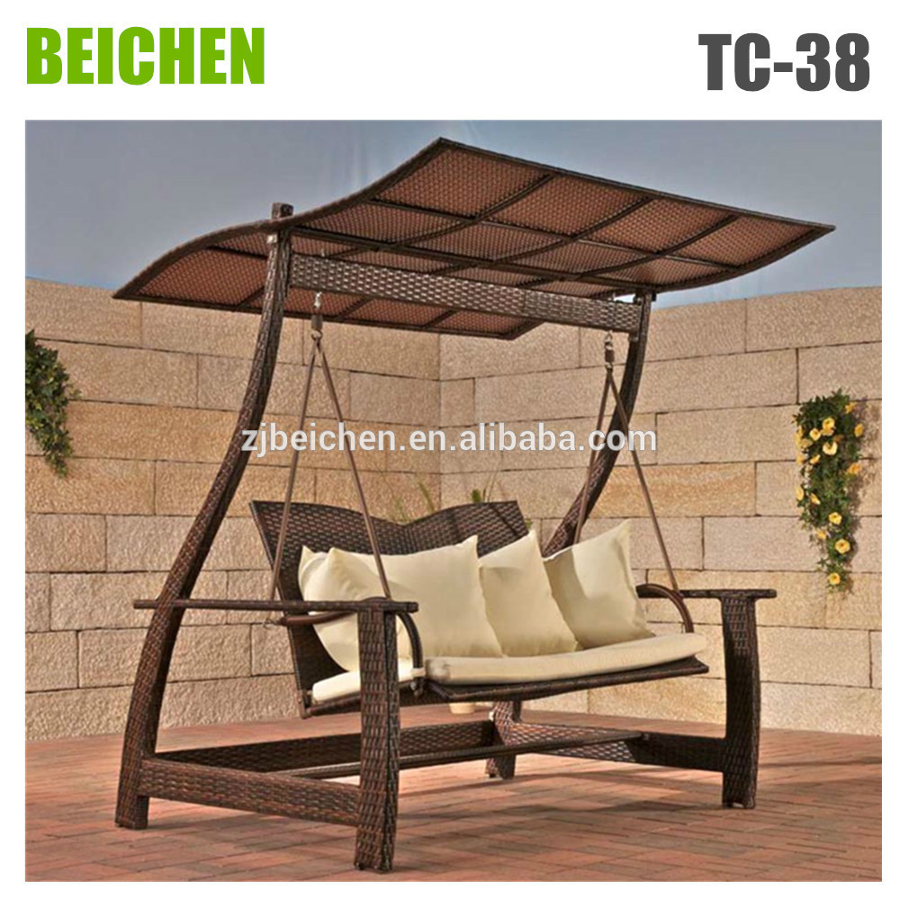 brown wicker swingasan chair with wheat cushion and curved roof ideas