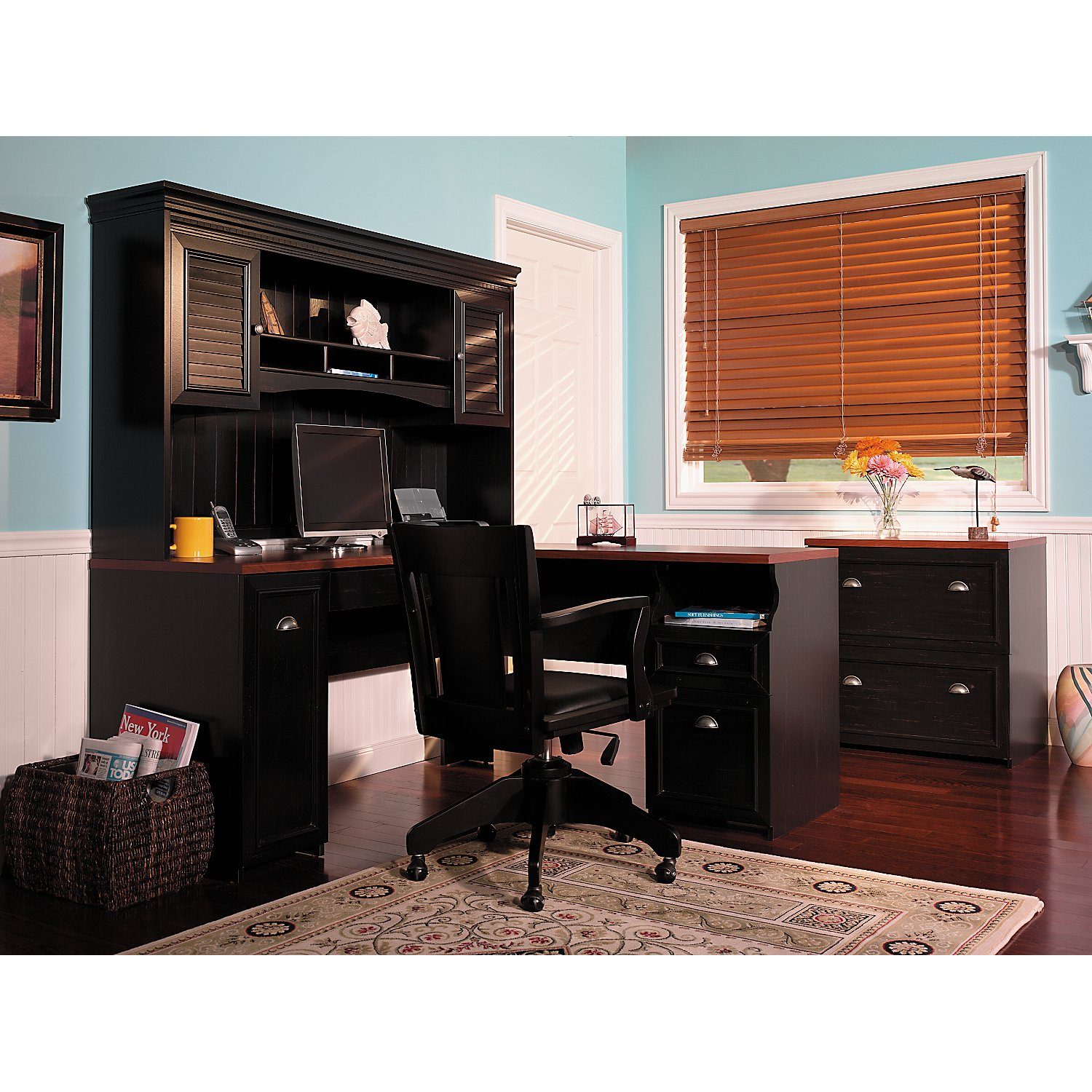 Bush Cabot L Shaped Desk With Hutch in black with drawer and computer set plus black armchair on an office home room with wooden floor plus carpet and blue wall