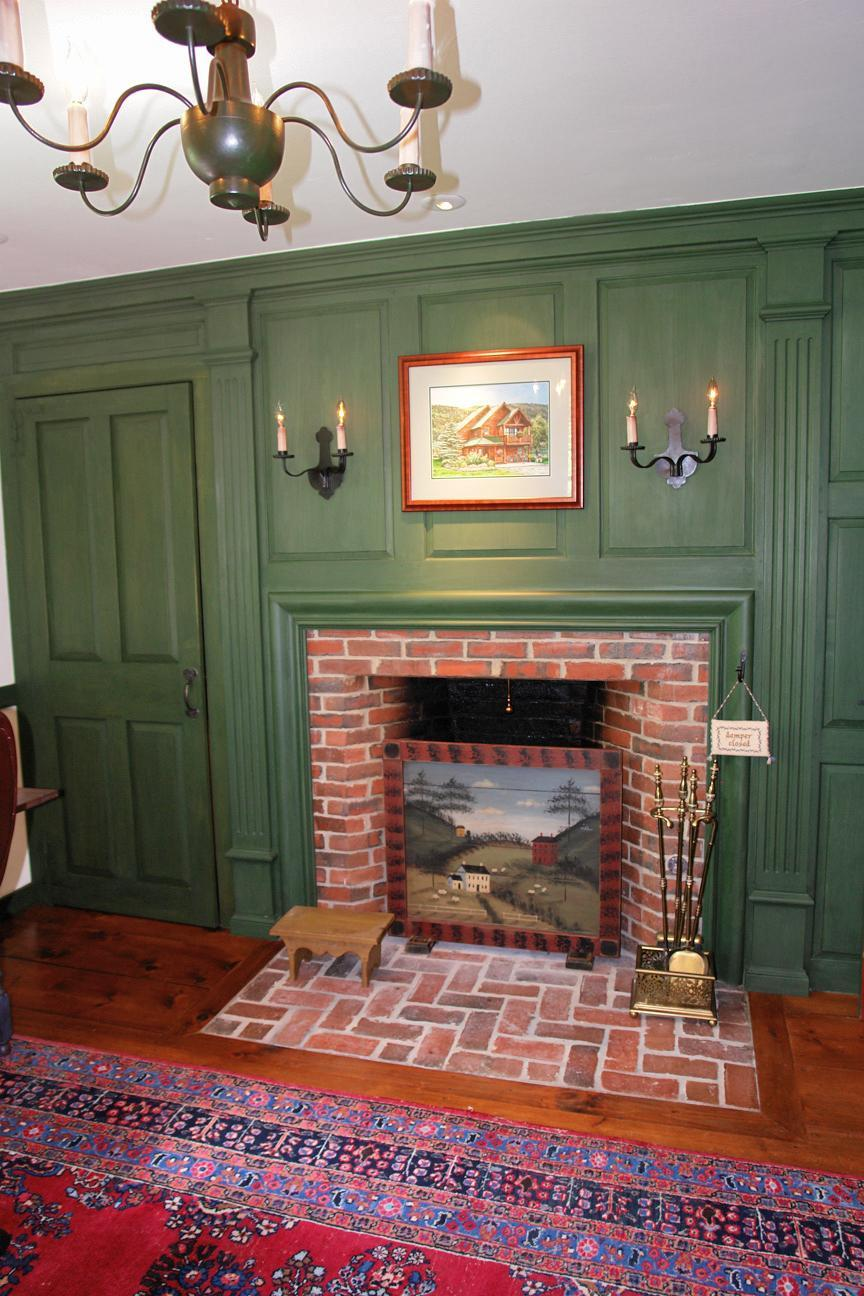 charming Rumford Fireplace with red and black frame and brivk mantel kit matched with green wainscroting and wooden floor for heat warming room decor ideas