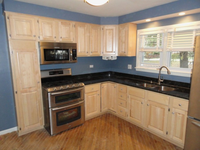 Cream Kitchen Cabinet Refacing With Black Countertop Plus Oven And Sink Under The White Window For Kitchen Ideas With Wooden Floor