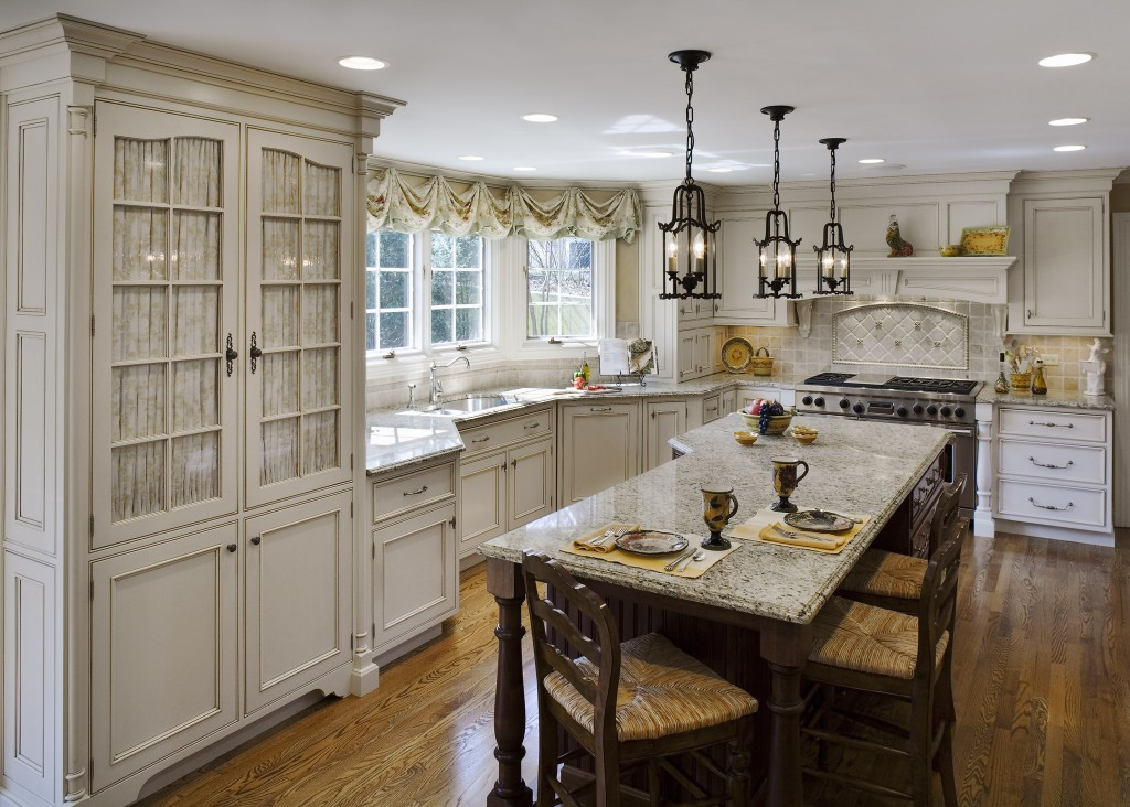 Custom cabinets with white Thomasville Cabinets with sink and oven plus dining table on white floor ideas