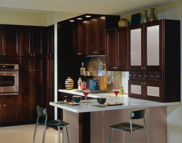 dark brown Thomasville Cabinets with silver handle and white countertop plus oven and bar table for kitchen decor ideas