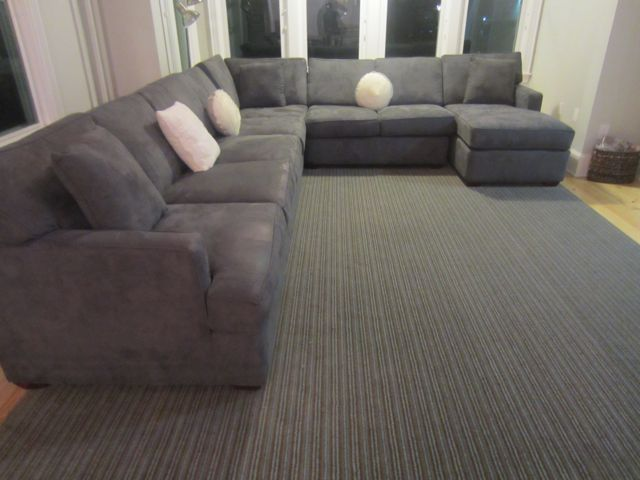 dark grey sectional couches with cushions on wooden floor plus carpet for living room decor ideas