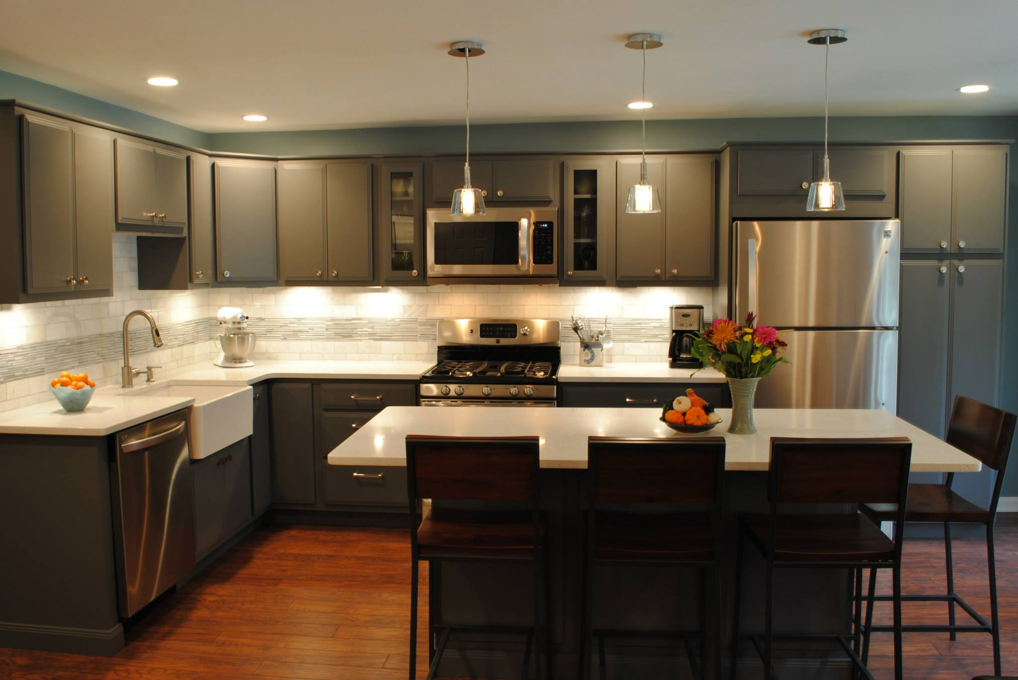 dark khaki aristokraft cabinets matched with white back splash plus oven and wooden floor for kitchen decoration ideas