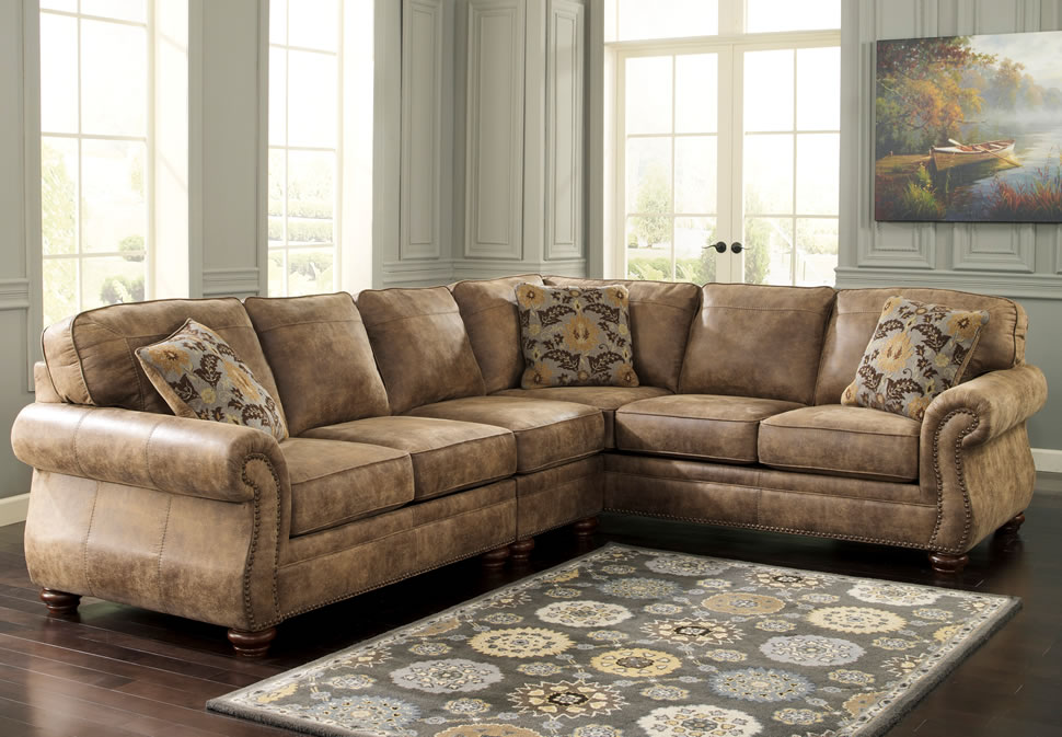 elegant brown leather Sectional Couches with floral cushions on wooden floor plus carpet for living room decor ideas