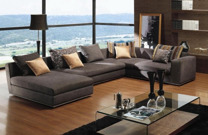 Elegant Dark Grey Sectional Couches With Cushions On Wooden Floor Plus  Black Carpet And Glass Table