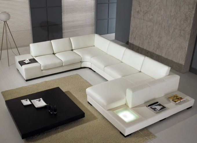 Elegant White Leather Sectional Couches With Black Coffee Table On Wheat Floor Plus Carpet For Inspiring Living Room Decor Ideas