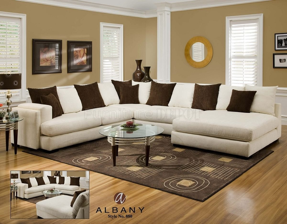 elegant white Sectional Couches with brown cushions plus round glass surface table on wooden floor plus carpet for living room decor ideas