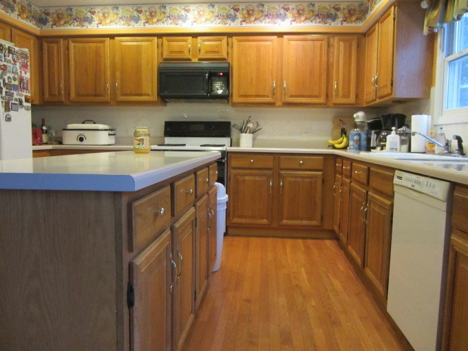 Goldenrod Aristokraft Cabinets Matched With Wooden Floor And White Back Splash Plus Oven For Kitchen Decor Ideas