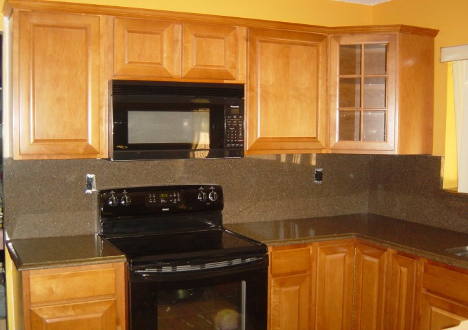 Goledenrod Thomasville Cabinets With Tan Countertop And Burlywood Back Splash Plus Black Oven For Kitchen Furniture Ideas