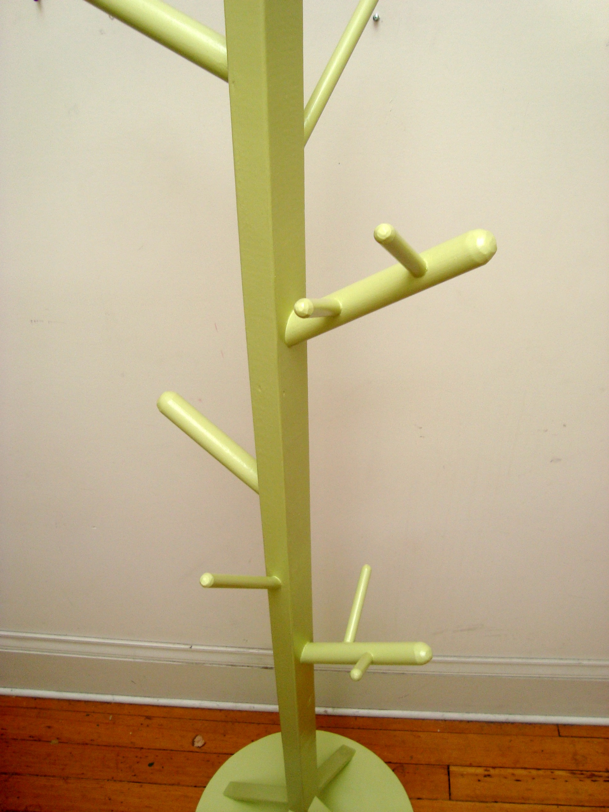 green standing coat rack with branch design hooks