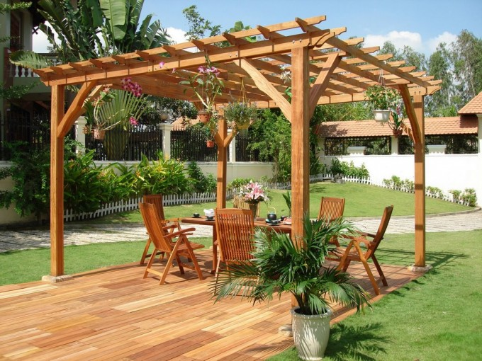 Home Garden Arbor And Pergola Plans With Wooden Chairs And Table Plus Wooden Floor And Hanged Orchid On Top