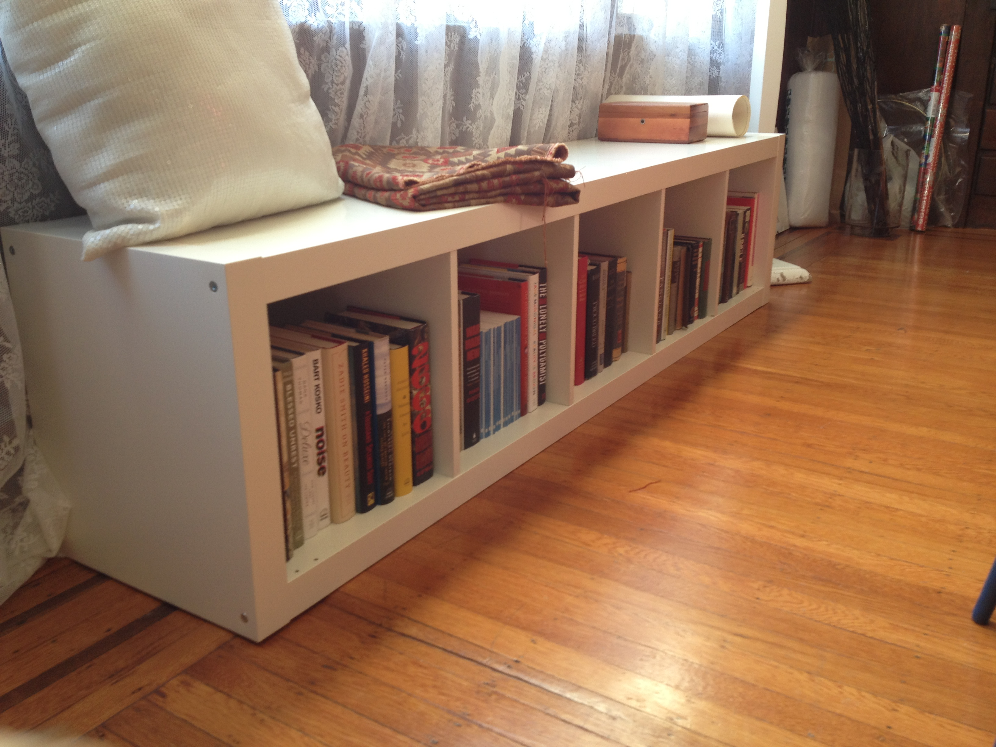 Ikea Expedit Bookcase in cream filled with books on wooden floor plus white cushion and white curtains