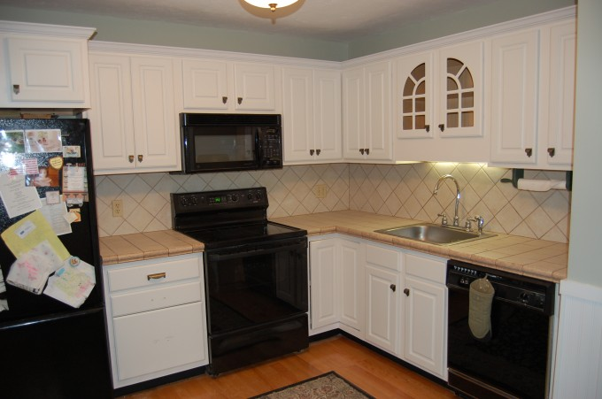 Lovable Kitchen Cabinet Refacing In White Plus Black Oven And Black Frige Plus Sink Plus Lovely Lamp On White Ceiling