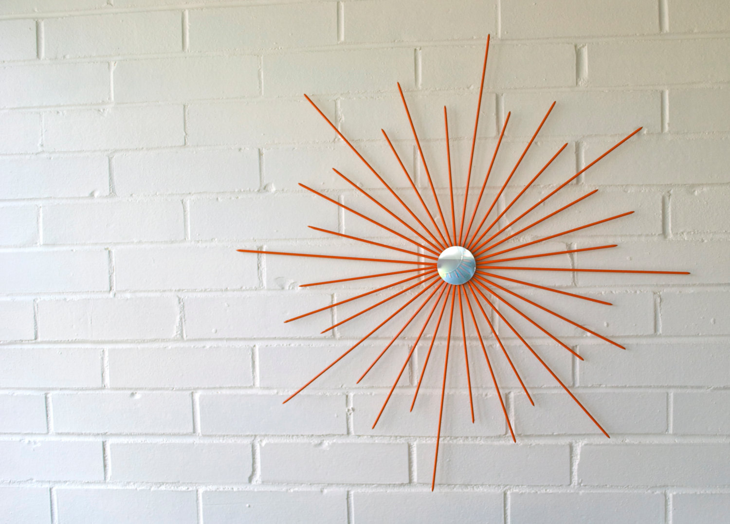 Mid Century Modern orange starburst wall decor on white wall ideas