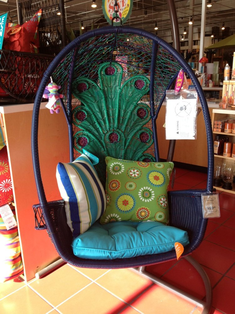 navy rattan swingasan chair with peacock tail motif on back plus colorful cushion ideas