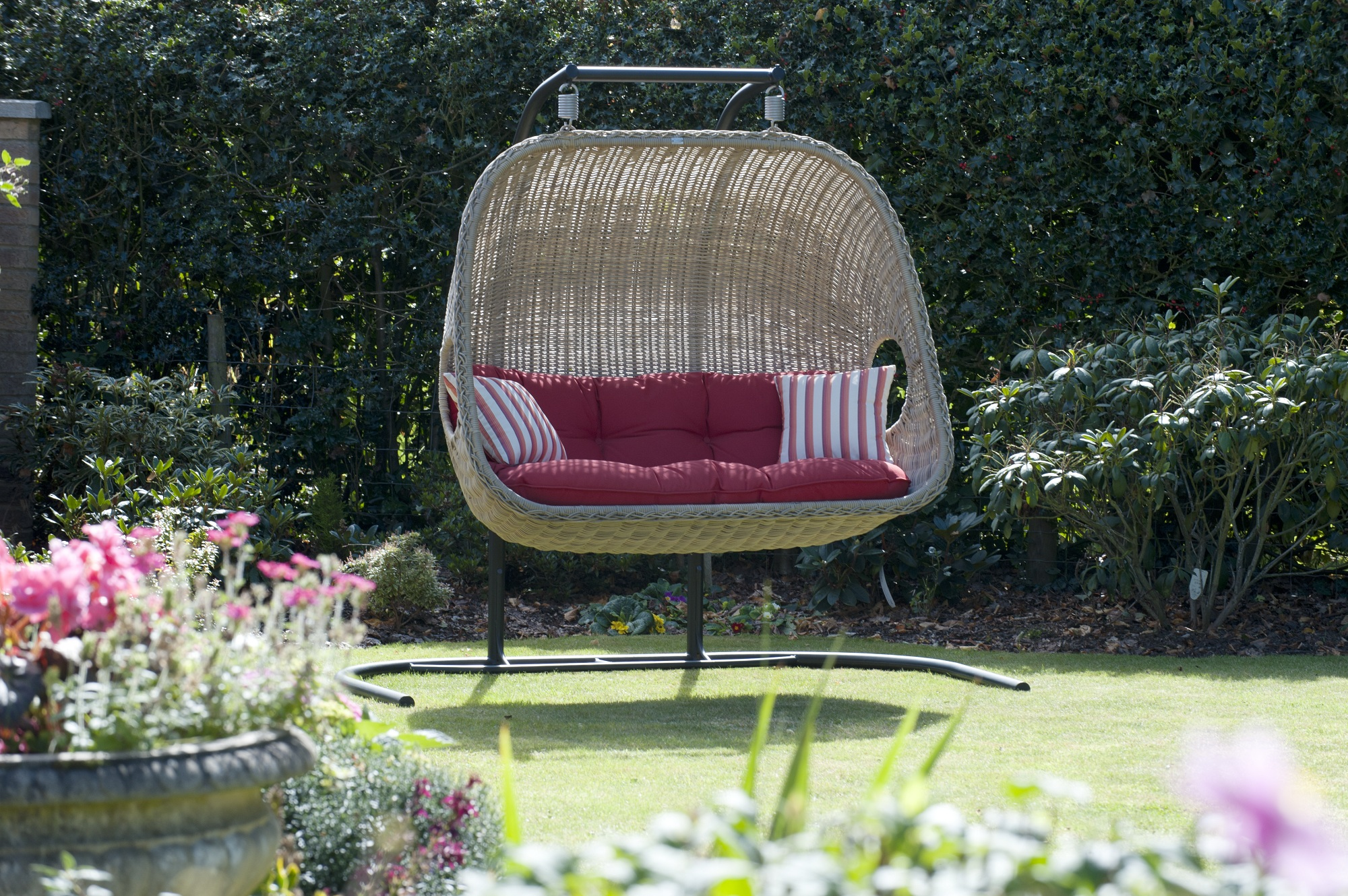 outdoor cream rattan swingasan chair with red seat cushion