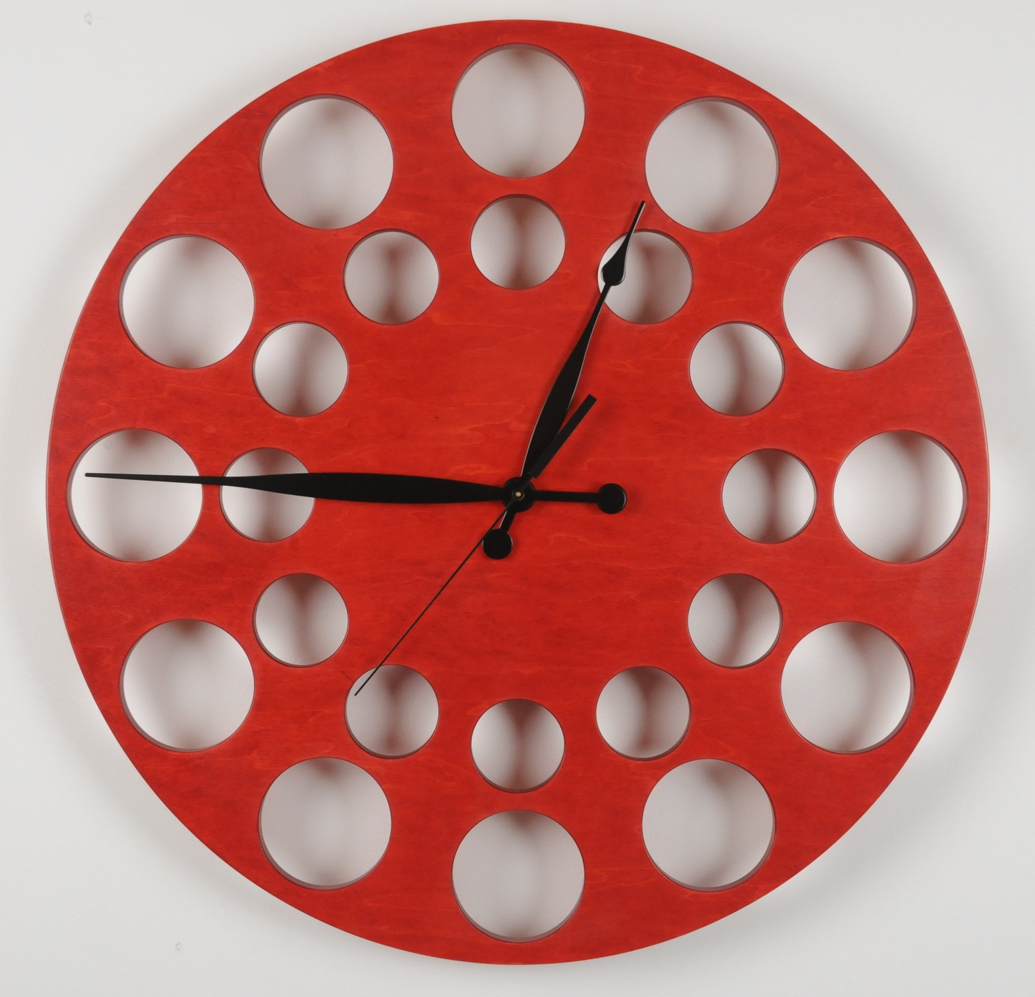 red oversized wall clock with dotted hall and black hand without numeral