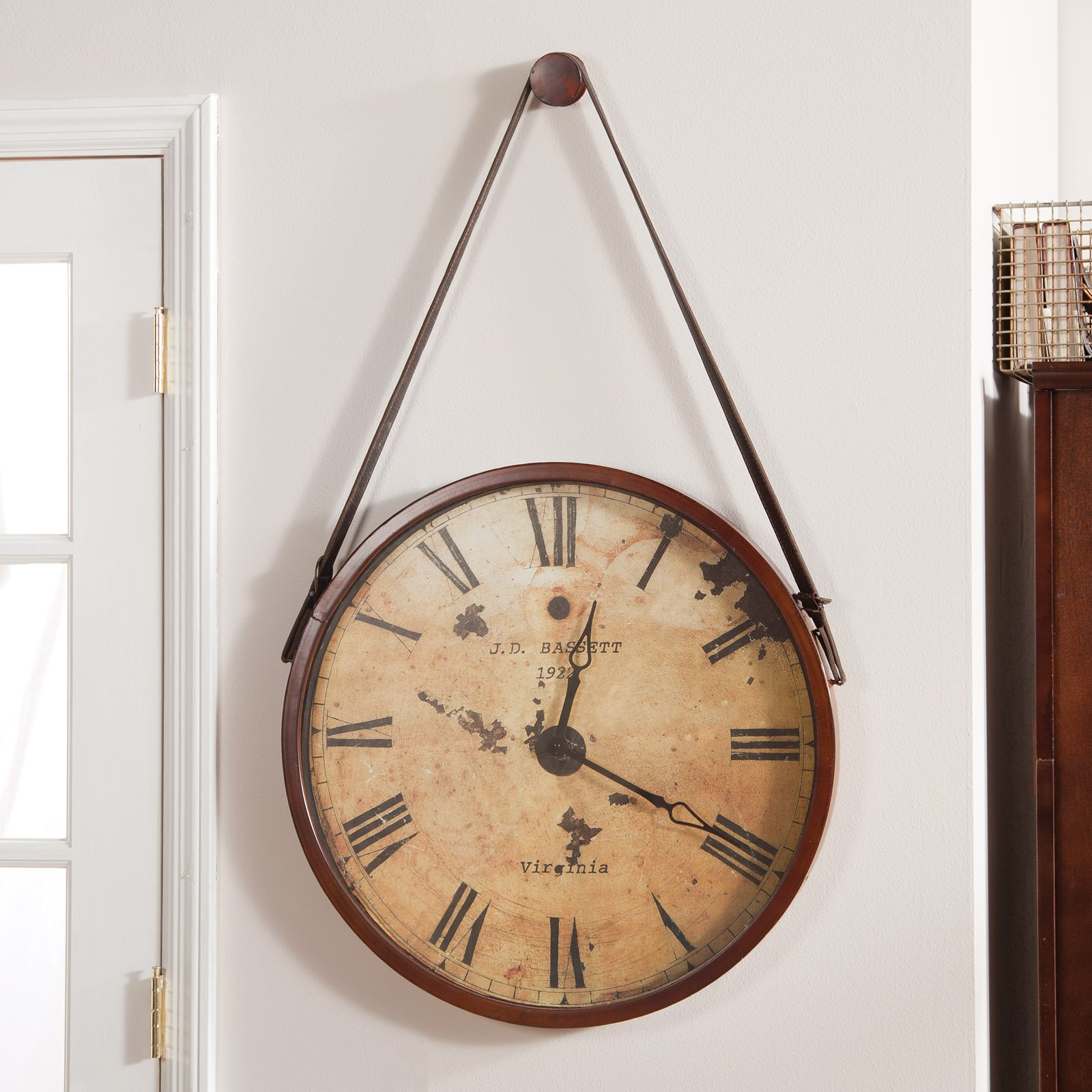 round oversized wall clock with strap on white wall