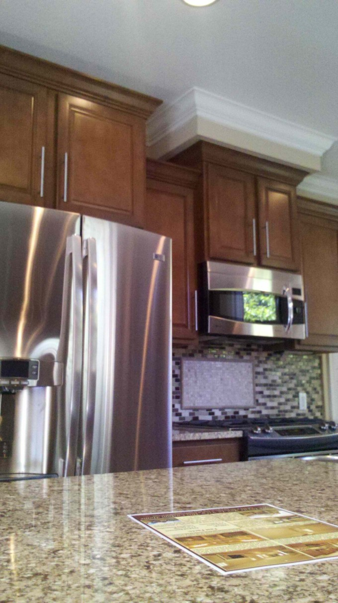 Sienna Aristokraft Cabinets With Mosaic Tile Back Splash Plus Frige For Kitchen Decor Ideas