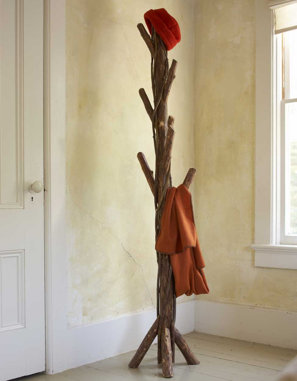 Twisted Vine standing Coat Rack on the corner of a room near thw white window