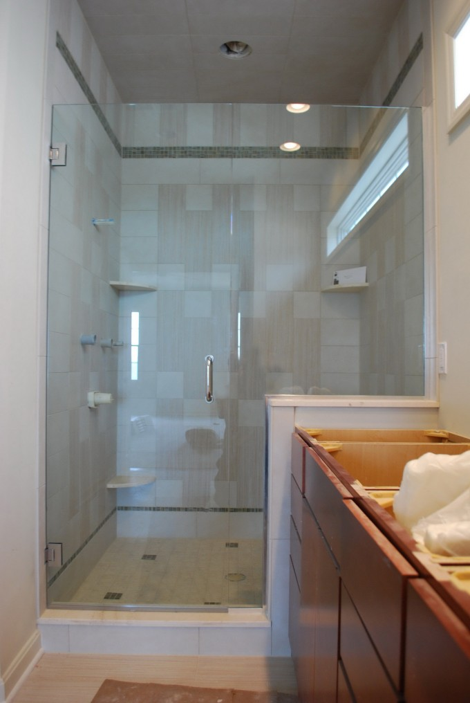 Upscale Frameless Shower Doors With Silver Handled Matched With Wheat Wall And Floor Plus Brown Dresser